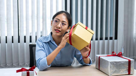 Young asian woman holding a presents box while sitting at office workspace and wrap gold gift box with red ribbon to preparing enjoy celebration on christmas festival
