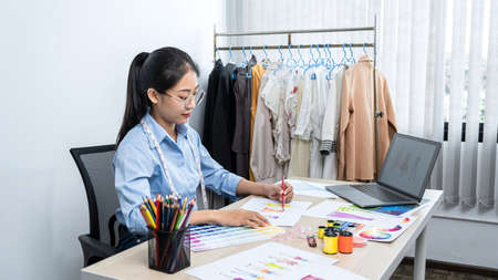 Asian woman fashion designer is design for new collection and drawing to coloring clothes sketch of dress with designing equipment while sitting to working in her workshop