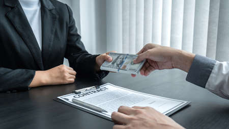 Dishonest cheating in business illegal money, Business woman giving bribe money in business people to give success the deal contract of investment, Bribery and corruption concept.