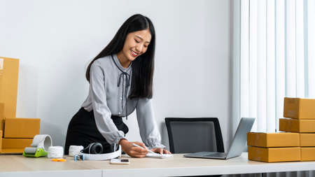 Young business woman entrepreneur smiling and writing order on notebook, courier checking address client and preparing packing product to many parcel box sending home delivery by post office