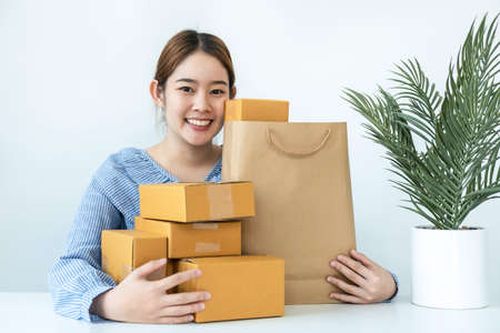 Asian woman small business owner smiling with many parcel of box to preparing order delivery to customer at home while sitting to working in home office