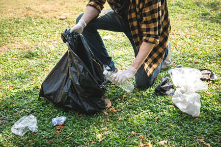 Volunteer man in gloves sitting to picking up plastic bottle and plastic waste into plastic black bag for cleaning the park during environmental activity to collecting garbage