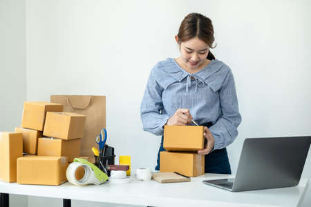 Asian woman small business owner standing to writing customer address on parcel of box and checking information on laptop while packing product deliver to client at home Reklamní fotografie