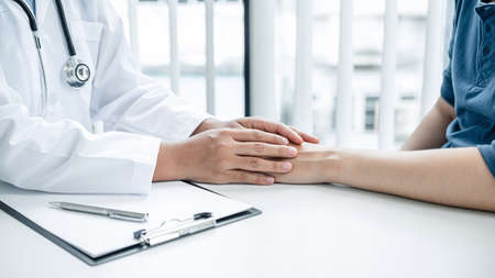 Doctor holding hands on patient about bad news at consulting room, to encourage, to supporting,  to fight for disease and to advice treatment and medicine at his hospital office
