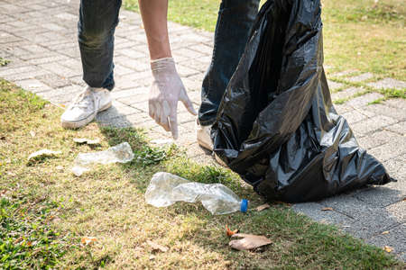 Volunteer man in gloves walking and stopping to collect plastic bottles into plastic black bag for cleaning the park during environmental activity to collecting garbage