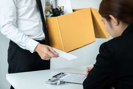 Business man employee holding brown cardboard box and sending a letter of resignation to the executive during boss sitting to writing contract document in office Reklamní fotografie