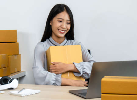 Young business woman entrepreneur is smiling and holding parcel box, courier is reading purchase online order on laptop and preparing packing product sending home delivery to client at home office