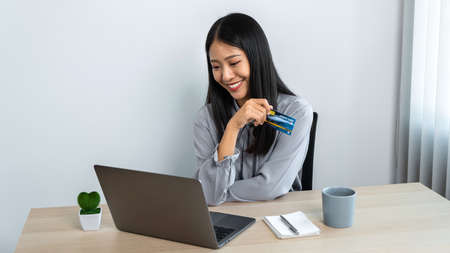 Young asian woman holding credit card and looking on laptop to using for online shopping while smiling and entering information for purchase order to online payment on website Reklamní fotografie