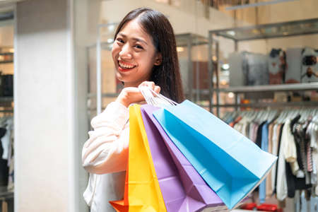 Portrait of asian woman shopaholic smiling and holding with many colorful shopping bags after just end up shopping and payment by credit card in shopping mall