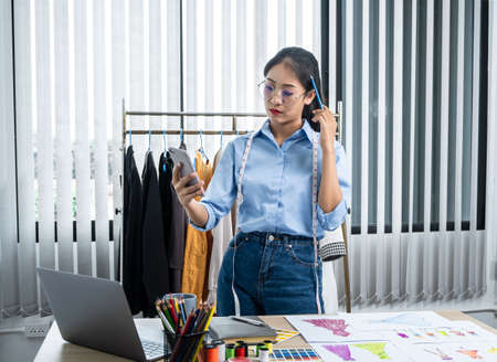 Asian woman fashion designer looking video on smartphone and thinking new clothes collection while standing to working at her workshop