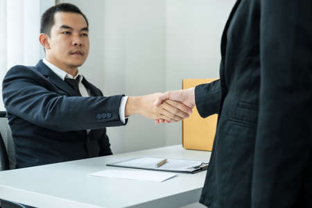 Business woman employee in suit shaking hands with boss after signing on resignation letter and carrying packed personal belongings in brown cardboard box putting on the table in office