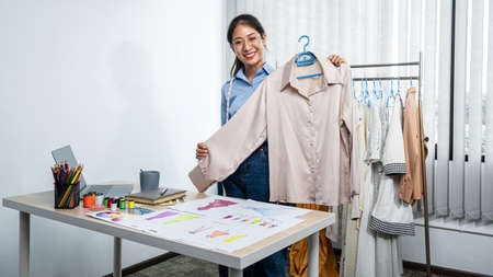 Asian woman fashion designer holding new clothes in hanger and looking at the camera to showing new clothes collection while standing to working in her workshop