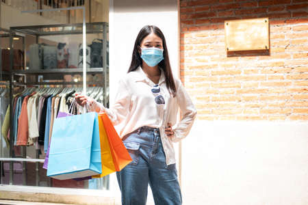 Asian woman shopaholic wearing face mask with many colorful shopping bags after just end up shopping and payment by cash in shopping mall