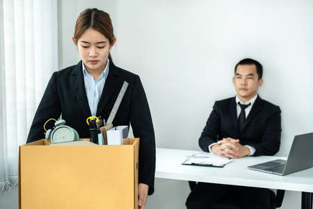 Business woman employee in suit is stressed and carrying personal belongings in brown cardboard box to walking out workplace after sending resignation letter to executive in office