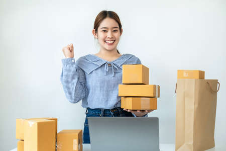 Asian woman small business owner standing and smiling to raise arm when job finished after receive order from customer and packing product to parcel of box at home office for delivery to client Reklamní fotografie