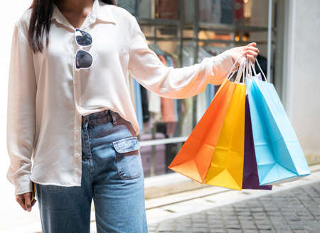 Close up of asian woman shopaholic hand with many colorful shopping bags after just end up shopping and payment by cash in shopping mall