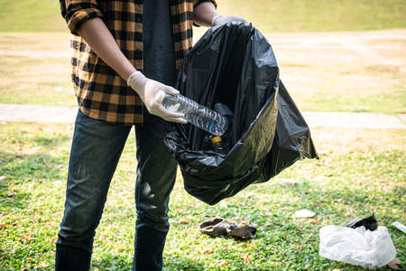 Volunteer man in gloves to picking up plastic bottle into plastic black bag for cleaning the park during environmental activity to collecting garbage
