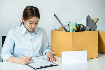 Business woman employee writing and signing on resignation letter before sending to executive while sitting on the table with personal belongings packed in brown cardboard box in office