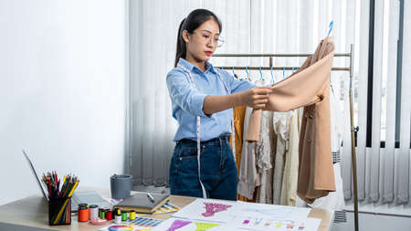 Asian woman fashion designer holding new clothes in hanger and looking on new clothes collection while standing to working in her workshop