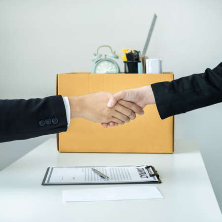 Close up of business woman employee in suit shaking hands with boss after signing on resignation letter and carrying packed personal belongings in brown cardboard box putting on the table in office