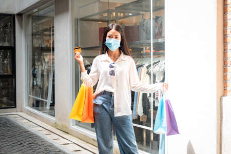 Asian woman shopaholic wearing face mask with many colorful shopping bags and holding credit card for payment in hand at shopping mall