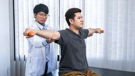 Young asian physiotherapist stretching the arms of man patient holding a dumbbell in hands during rehabilitation therapies and treatment of physiological disorders in clinic