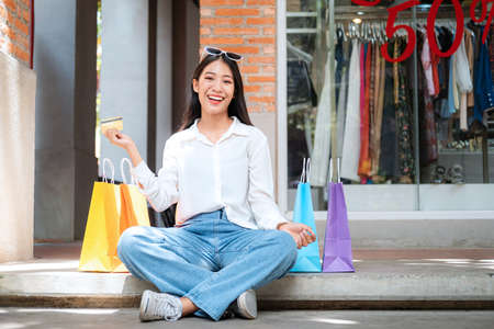 Asian shopaholic woman wearing sunglasses headband with many colorful shopping bags and holding credit card while sitting to rest after make purchase and payment heavy shopping in shopping mall