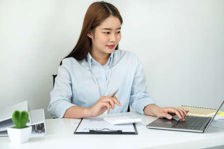 Woman office worker reading and typing business project report on laptop after that taking note of information on notebook while sitting to work hard for new business in office Standard-Bild