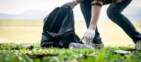 Volunteer man in gloves walking and stooping to collect plastic bottles into plastic black bag for cleaning the park during environmental activity to collecting garbage