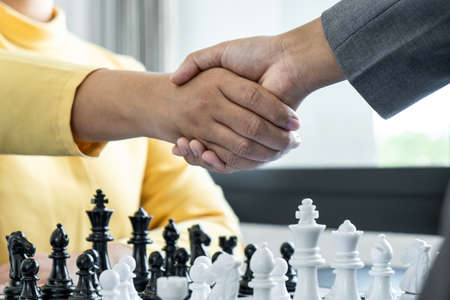 Businessman shaking hands after playing chess and thinking about strategy crash overthrow the opposite team and development analysis for win and successful. Standard-Bild
