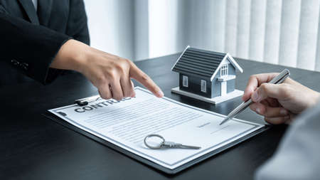 Estate agent broker presentating to client decision signing agreement contract real estate with approved mortgage application, buying mortgage loan offer for and house insurance. Standard-Bild
