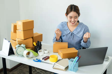 Asian women small business owner looking information order on laptop and raise two arms when job finished after receive order and packing product in box of parcel delivery to customer at home