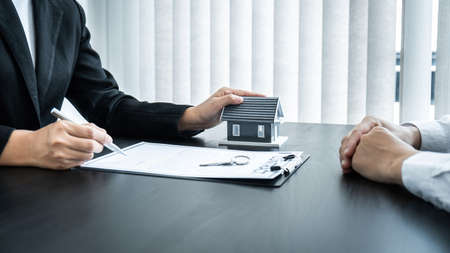 Estate agent giving house and keys to client after signing agreement contract real estate with approved mortgage application form for or house insurance.