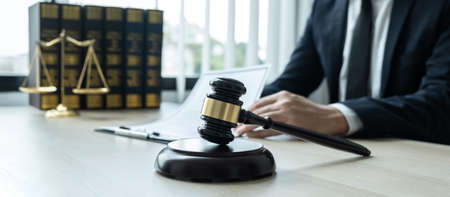 Counselor lawyer or notary working on a documents and report of the important case and wooden gavel, brass scale on table in courtroom.