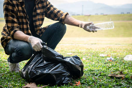 Volunteer man in gloves sitting to picking up plastic bottle into plastic black bag for cleaning the park during environmental activity to collecting garbage Standard-Bild