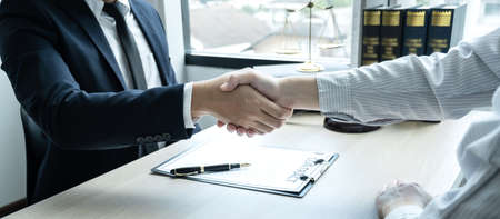 Handshake after consultation between a male lawyer and client, giving advice and prosecutions about the regarding estate.