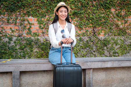 Asian woman tourist sitting on the chair with hat and holding her luggage to preparing on holiday trip while looking on the camera and waiting get to the airport Standard-Bild