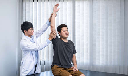 Young asian physiotherapist are examining the bones to abnormal muscular symptoms physical to rehabilitation therapies and treatment of physiological disorders for man patient in clinic