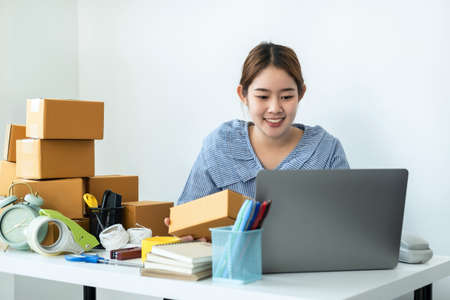 Asian woman small business owner holding box of parcel in hands and checking order on laptop while courier working with many boxes of parcel on the table to preparing delivery for customer at home