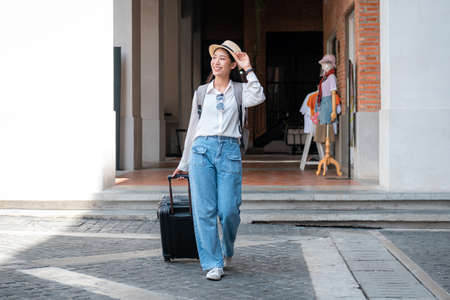 Asian woman tourist is traveling on holiday trip with hat and dragging her black luggage while walking to passengers lounge in the airport