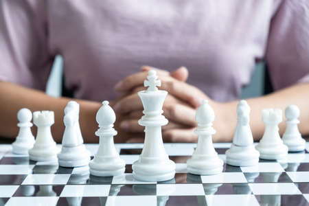 Woman playing chess and thinking strategy plan about crash overthrow the opposite team and development analyze for successful.