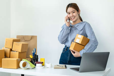 Asian woman small business owner holding parcel of box and talking with customer on smartphone to receive order while standing to preparing to packing product delivery to client at home