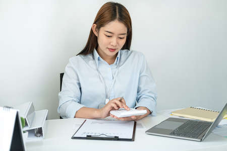 Woman office worker sitting to working and pressing a calculator to calculate the profit of a new business project and having happiness when job well done