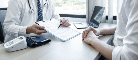 Doctor consulting with the patient and checking sickness condition while presenting results diagnosis symptom examining about the problem of illness and recommend treatment method.
