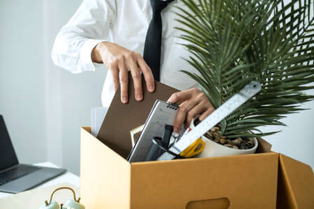 Business man employee packing notebook and picking up personal belongings into brown cardboard box to leaving workplace when resignation from work or changing work Standard-Bild