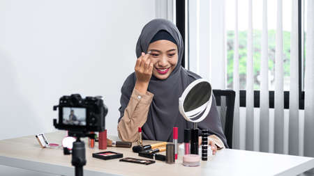 Asian muslim woman beauty blogger tutorial eyebrow techniques and making videos to review cosmetic products for her vlog and blogger to share on website or social media Standard-Bild