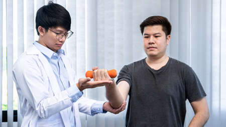 Young asian physiotherapist gives advice on how to properly lifting dumbbells during physical therapy sessions in the clinic Standard-Bild