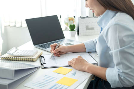 Woman office worker sitting to working and writing business project report on clipboard during checking information on document and smiling when job finished