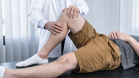 Young asian physiotherapist checking knee joint with injury to giving treatment and to rehabilitation therapies in clinic