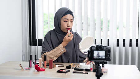 Asian muslim woman beauty blogger tutorial by lipstick makeup on her mouth and making videos to review cosmetic products for her vlog and blogger to share on website or social media